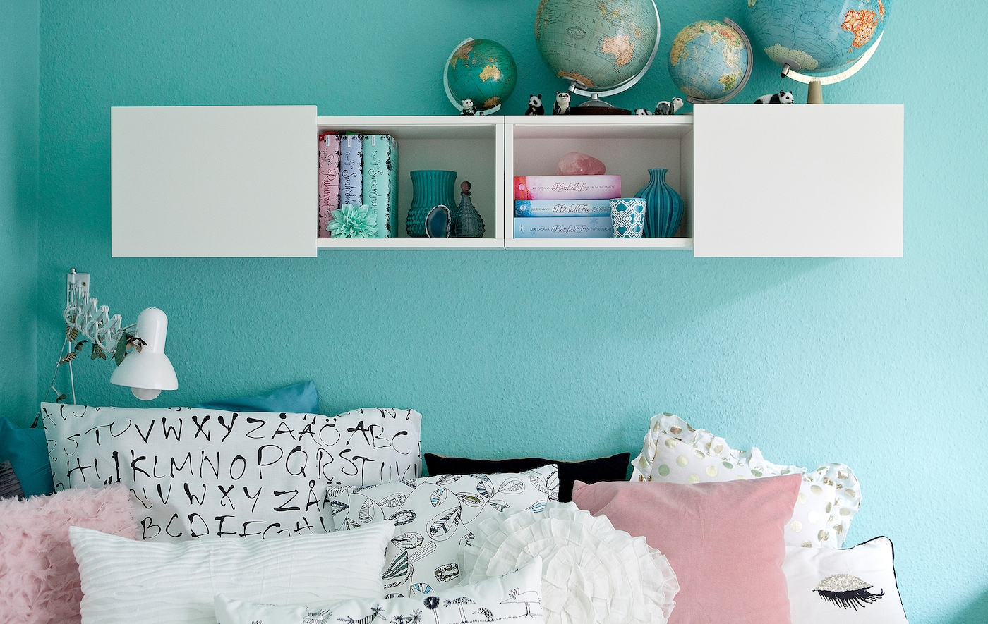 A room with pastel blue walls and monochrome textile.