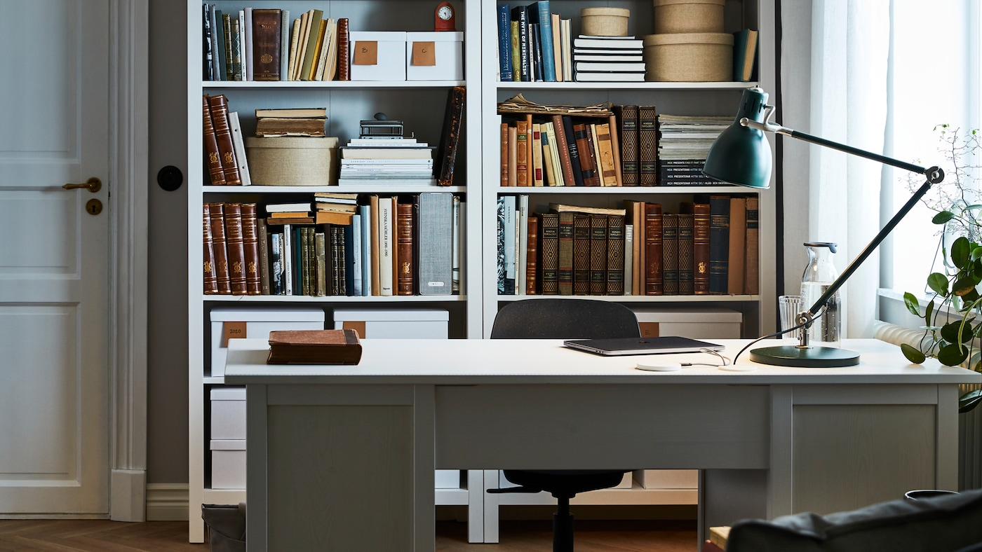 A room with two bookcases full of books and other diverse items, and a grey desk with white work top, a work lamp and a chair.