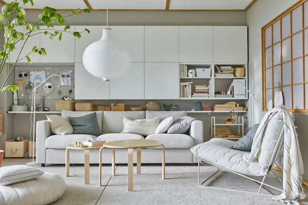 A room with white cabinets and a white sofa with two wooden nesting tables and a white pendant lamp hanging above.