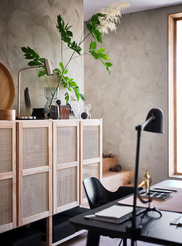 A room with window and lattice-fronted wall storage unit with plant and accessories on it and black desk, chair and lamp.