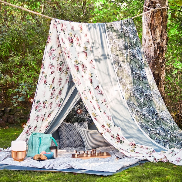 A rope between two trees and long pieces of fabric draped over the rope to create a summer tent for a picnic.