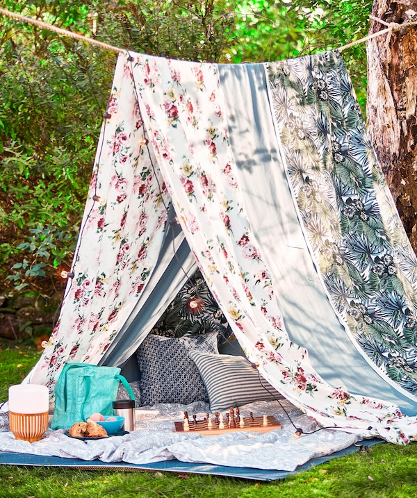 A rope between two trees and two large pieces of fabric hung over the rope to create a summer picnic tent.