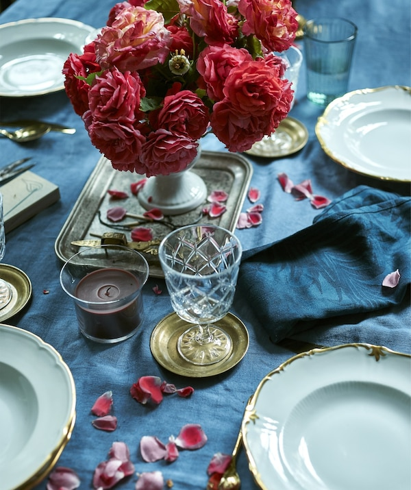 A rose centerpiece on a blue tablecloth, with plates, glasses and a candle.