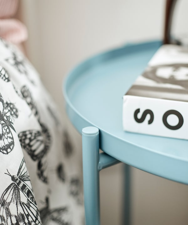 A round blue metal table with a book on top, beside a bed covered with a black and white duvet.