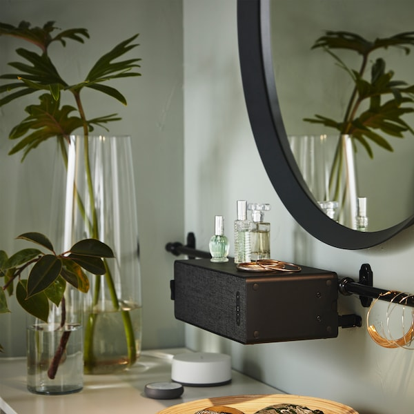 A round mirror, a black SYMFONISK WiFi speaker that hangs on a rail, plants in glass vases, some jewellery and perfumes.