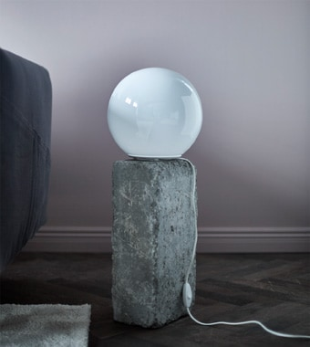 A round table lamp sitting on a rock