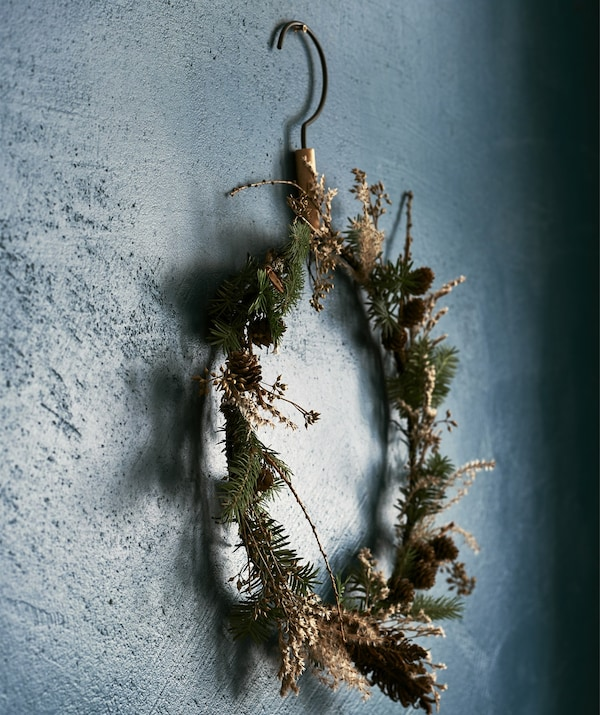 A round, thin winter wreath made from pine cones and woodland branches, hanging on a dark blue wall.