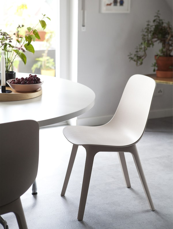 A round, white table and beige-and-white chairs.