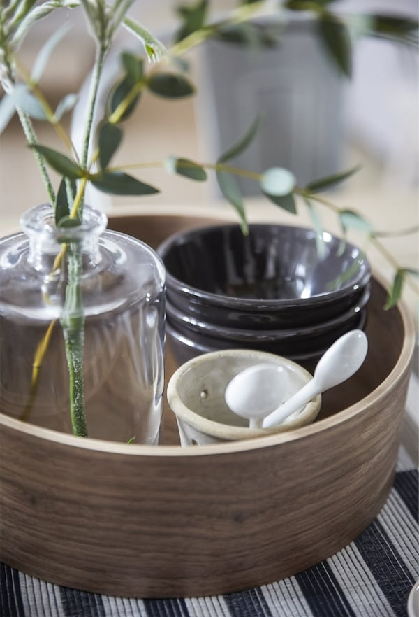A round wooden tray containing bowls and a vase with eucalyptus.