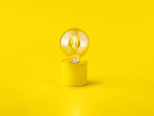 A round yellow light feature with a round vintage light bulb on a yellow background.