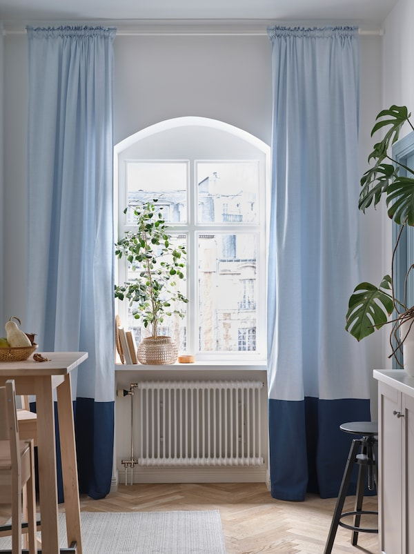 A rounded kitchen window with a large plant on the windowsill and light blue BENGTA block-out curtains on both sides.