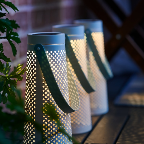 a row of VINDEN solar powered lanterns are sat  aluminating a outdoor decked terrace