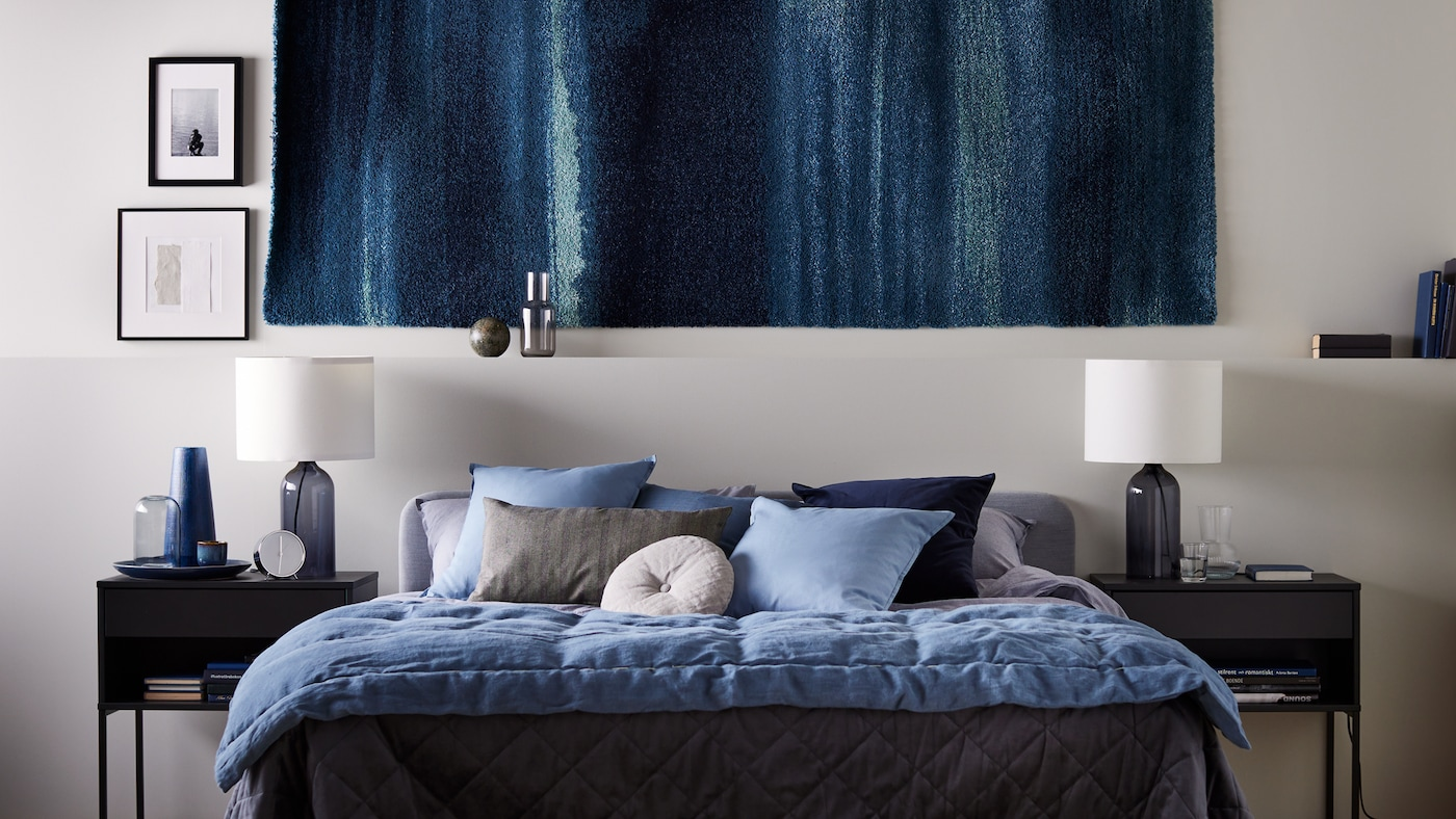 A rug on the wall, with VIKHAMMER bedside tables either side of a light-grey SLATTUM double bed, with KOPPARBLAD bed linen.