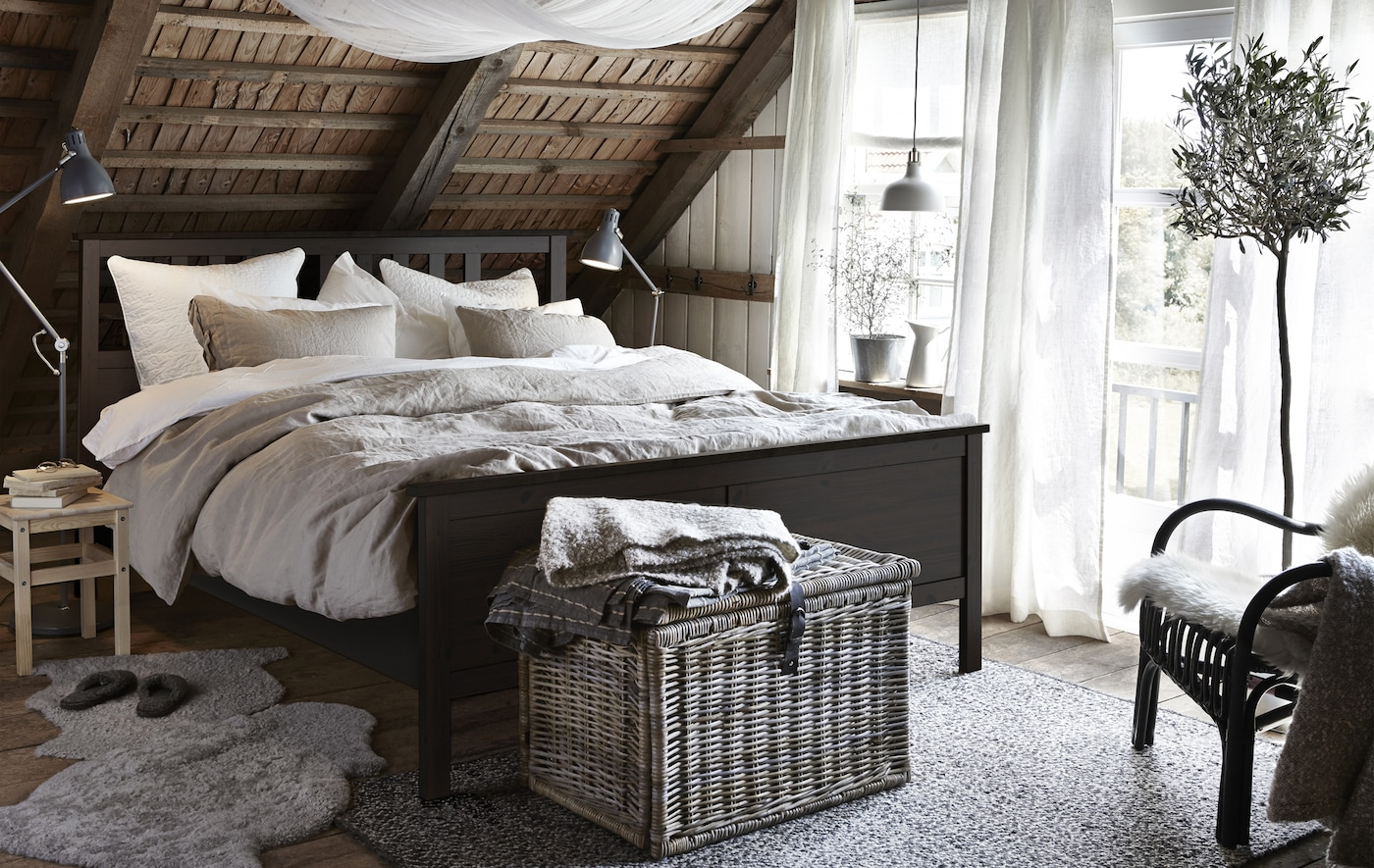 A rustic bedroom with a black-brown HEMNES bed frame, wicker basket, sheepskin on the floor, and sloped wooden ceilings.