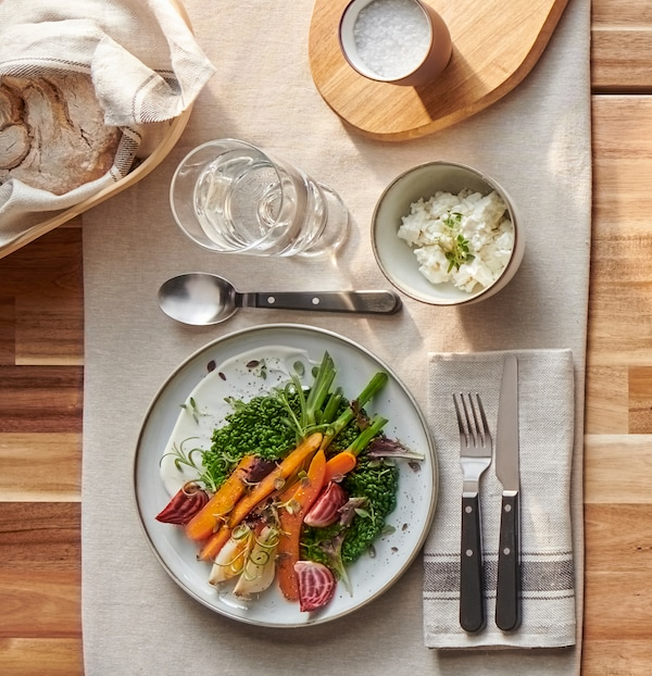A rustic, grey and brown plate with colourful vegetables, sturdy LIVNÄRA cutlery and a glass of water on a beige table cloth.