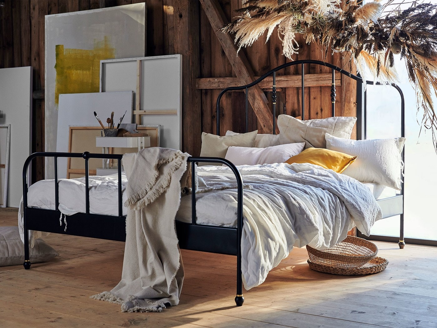A rustic loft space with a curvy, black SAGSTUA bed frame covered in neutral bed linen and with canvases leaning against a wall.