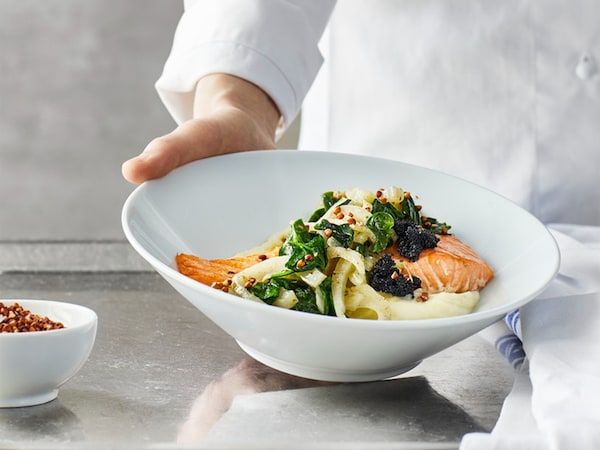A salmon dish with vegetables and mashed potatoes in a bowl.