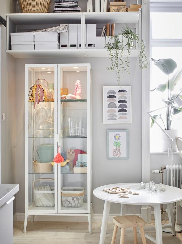 A sarokba tolva a magas, fehér MILSBO szekrény nyitott tárolókkal elfér a magas fali polcok alatt, így bőségesen van tárolóhely.