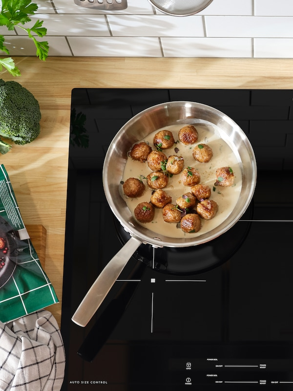 A sauté pan with meatballs and sauce inside stands on a black induction cooktop.