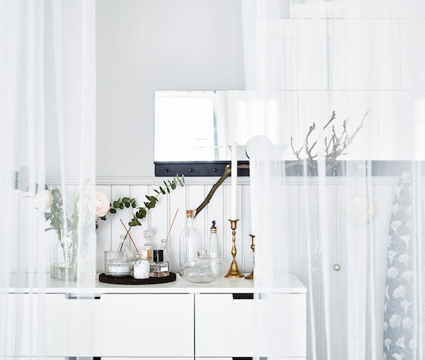 A scent station on top of a white dress unit with golden candlesticks and candles, flowers and perfumes.