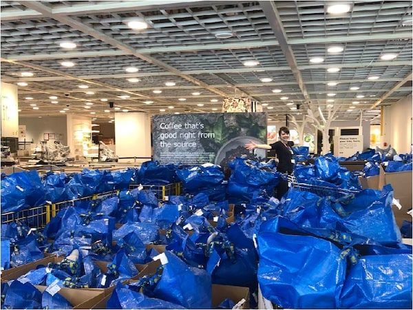 A sea of IKEA blue FRAKTA bags filled with donations