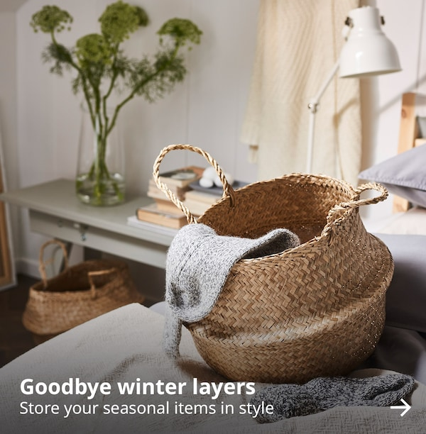 "A seagrass basket with a knitted sock draped on the side. There is text on the image that reads ""Goodbye winter layers. Store your seasonal items in style""."