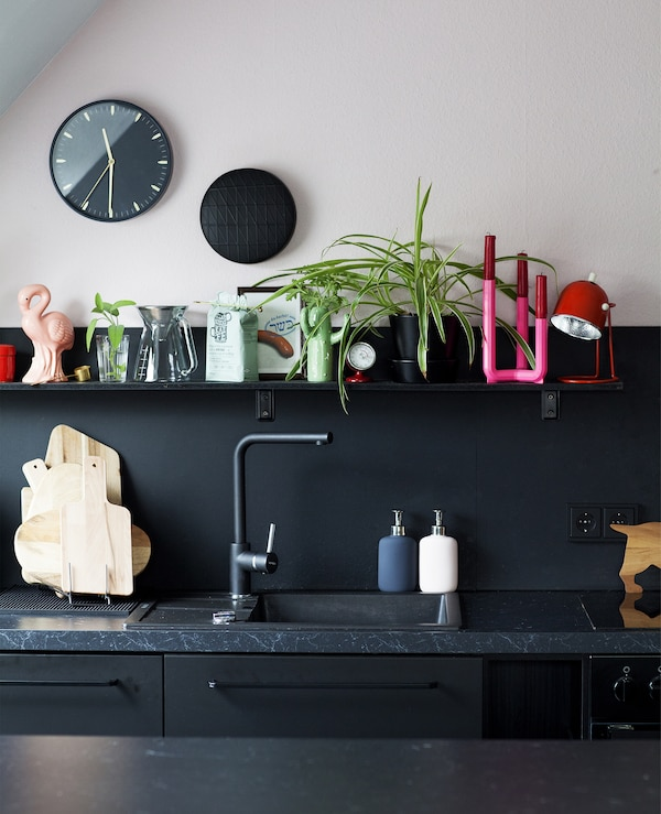 A section of a black-and-pink kitchen with open shelving above a sink.