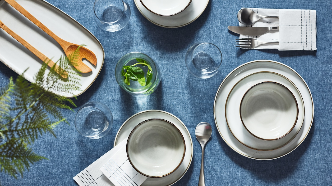 A section of a decorated table with grey GLADELIG plates and bowls, set on a dark blue SEVÄRD tablecloth.