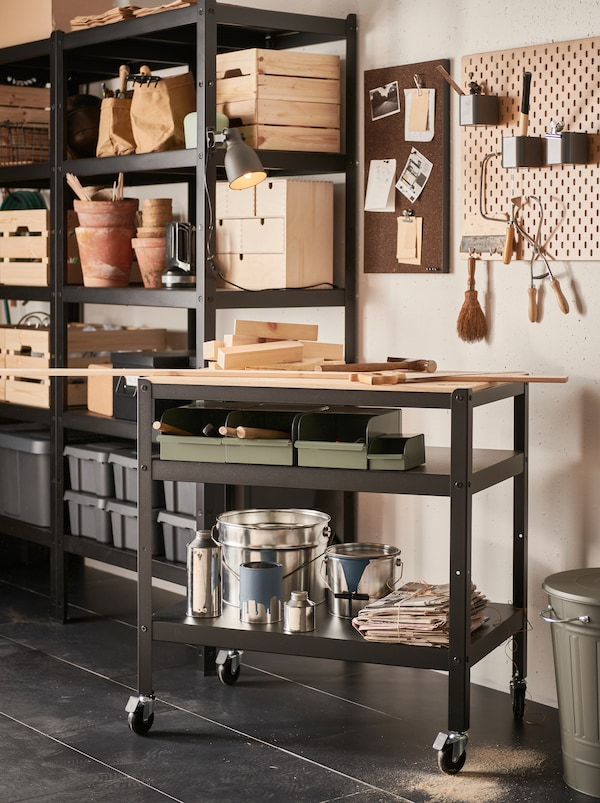 A section of a garage with a black BROR metal trolley with a wooden worktop and two shelves filled with boxes and paint cans.