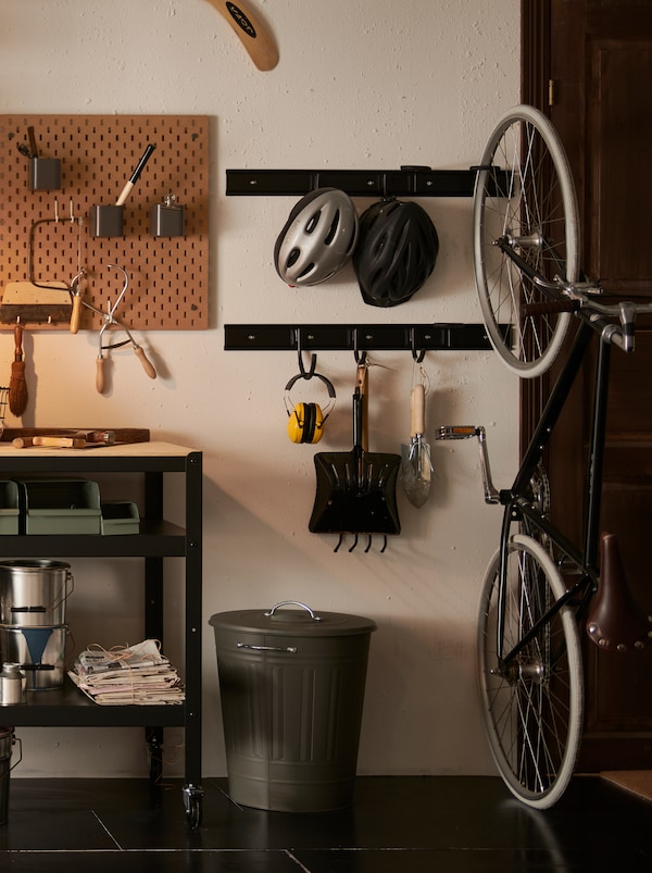 A section of a garage with a gray KNODD metal bin with a lid and garden tools hanging on black metal wall hooks.