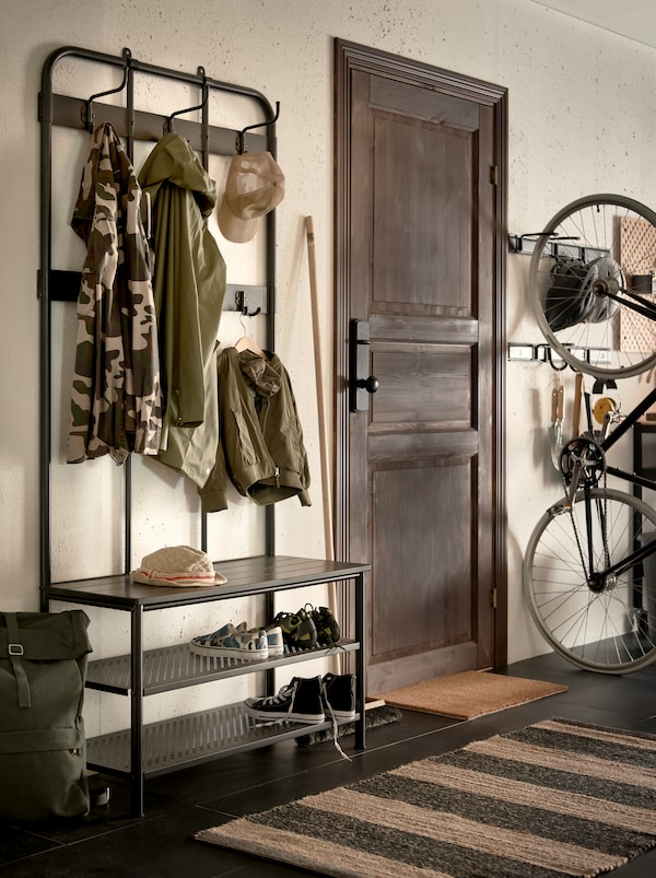 A section of a hallway with a black PINNIG metal coat rack with an incorporated shoe storage bench and clothes hooks.