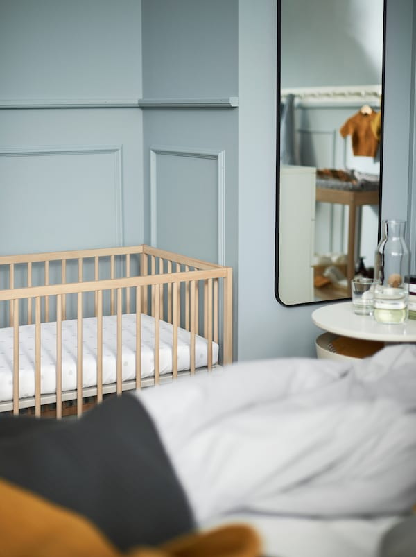 A section of a light blue bedroom with a white bedside table, a mirror and a SNIGLAR wooden baby cot.