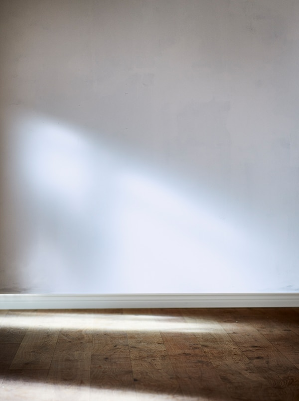 A section of an empty room with a white, unpainted wall and floor in natural wood. Sunlight falls in from the side.