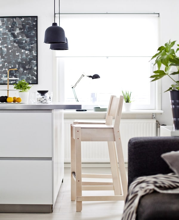 A section of white kitchen island with a pale-wood stool.
