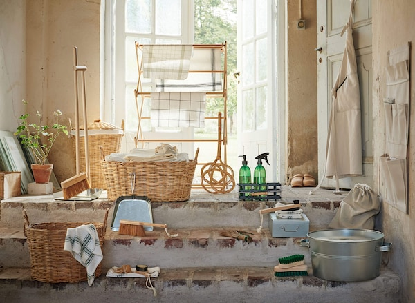A selection of BORSTAD products in the entry way of an old home- weaved baskets, a brooms and sweepers, and spray bottles.
