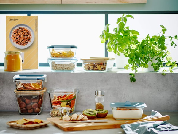 A selection of glass food container swith lids in front of a window with a wooden cutting board and some fruit.