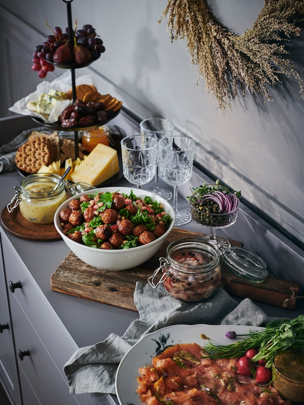A selection of IKEA food, including plant balls, salmon and crispbread, is arranged on a grey sideboard.