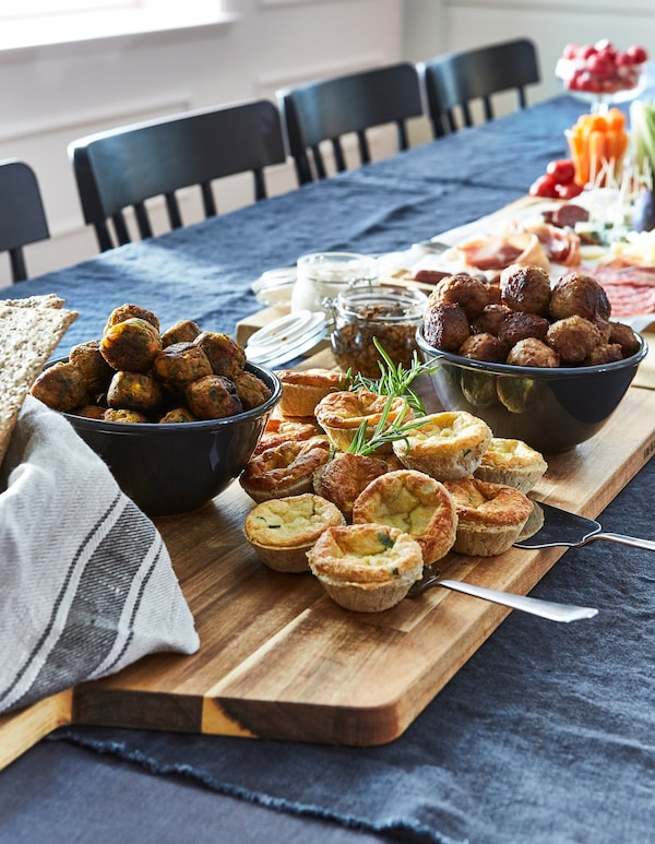 A selection of IKEA meatballs, cheese pies and veggie balls, arranged on chopping boards, on a dining table.