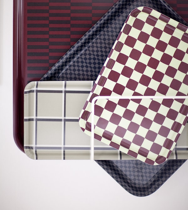 A selection of patterned trays fixed to a white wall.