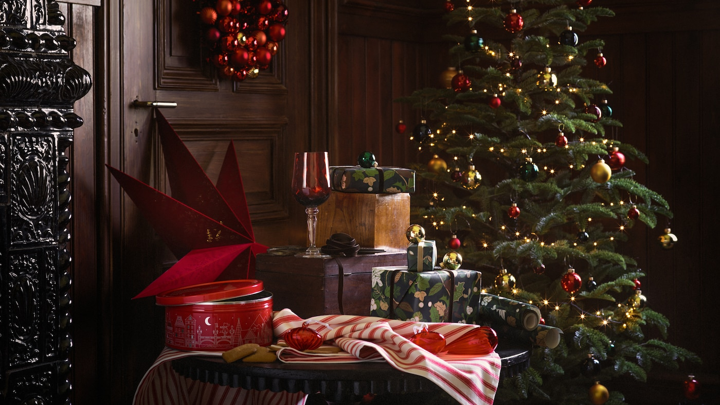 A selection of products stand in a wood-panelled room, including a Christmas tree, gift wrap and home accessories.