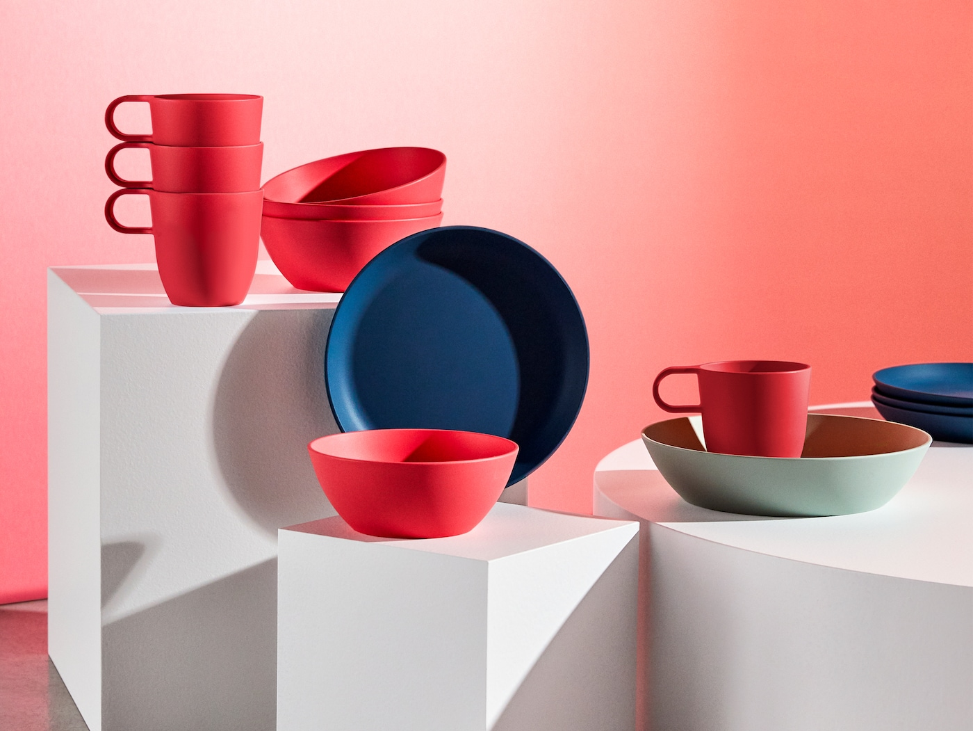 A selection of TALRIKA mugs, bowls and plates in bright red, light green and dark blue.