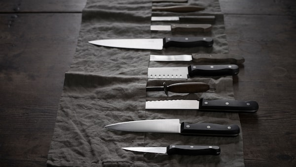 A selection of VARDAGEN kitchen knives in various sizes laying on a dark-gray knife roll.