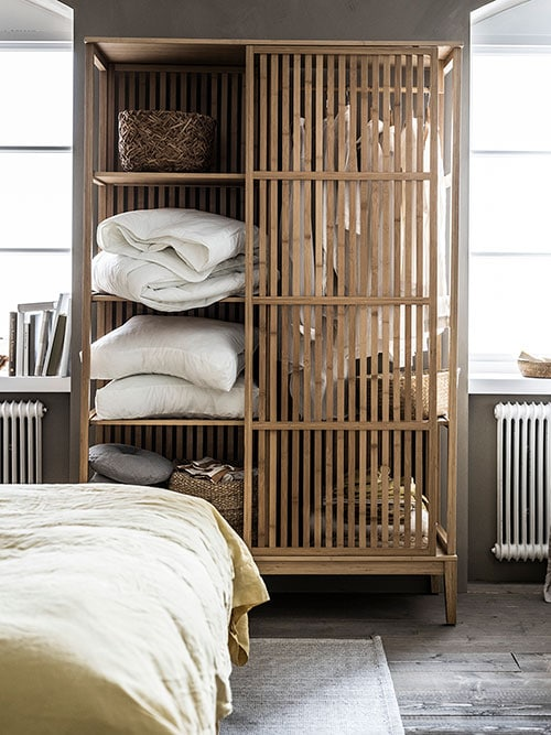 A semi-open bamboo wardrobe with shelves and hanging space, filled with clothing and bedlinen.