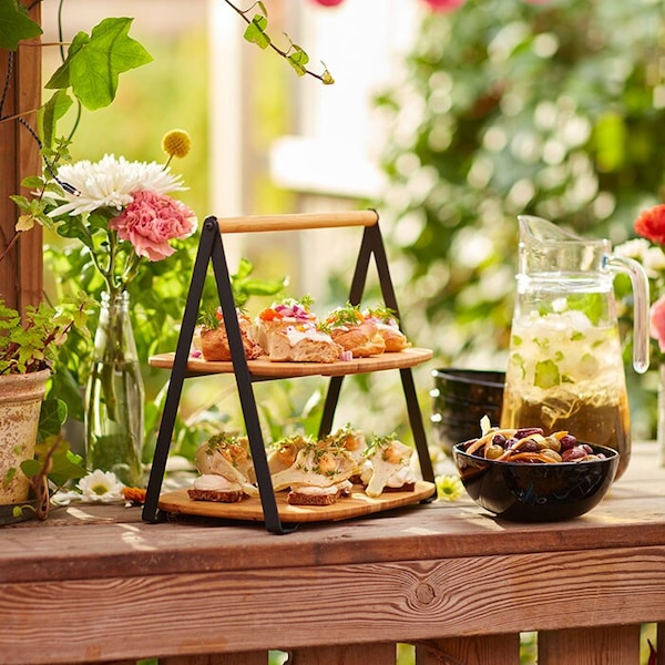 A serving tray with two layers of sandwiches and appetizers, placed on an outdoor table, with greenery in the background.