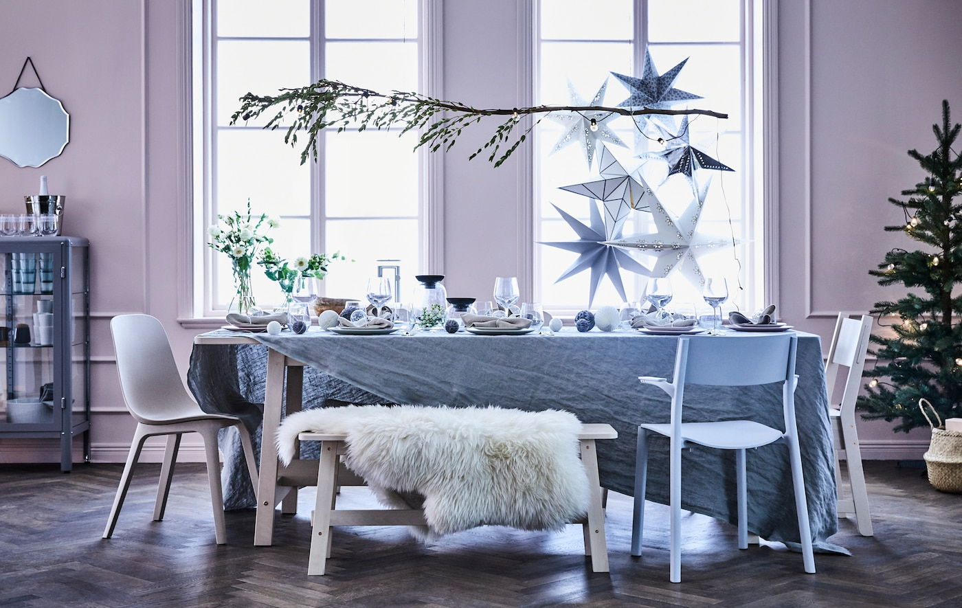 A set dining table with a bench and different chairs, over the table hangs a branch decorated with a lighting chain.