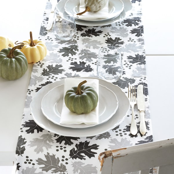 A set dining table with a grey and white table runner, pumpkins for decoration.