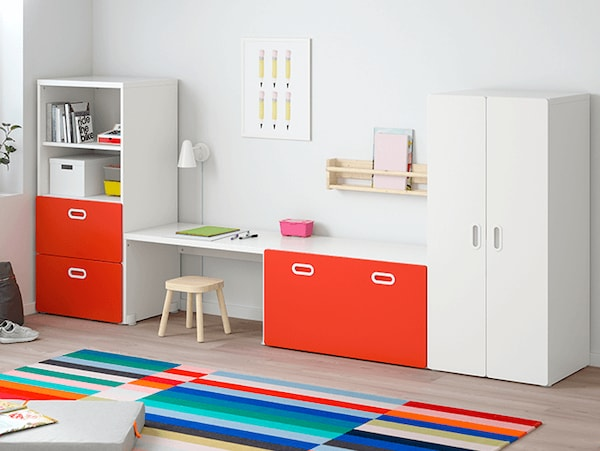 A set of cabinets with white doors and red drawers with a stool and a colorful striped rug.