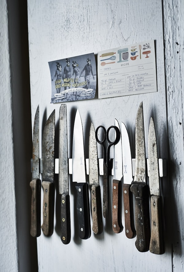 A set of vintage knives fixed to a kitchen wall.