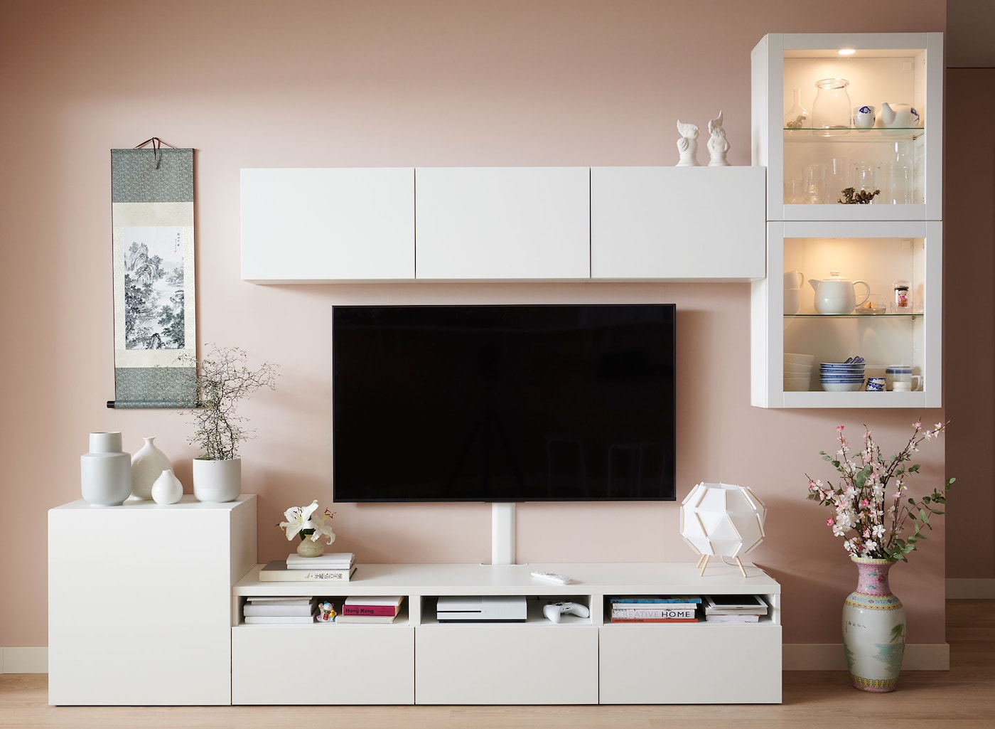 A set of white cabinets arranged on the ground and on the wall surrounding a TV mounted to the wall.