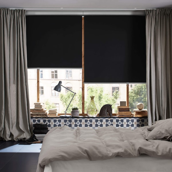A set of windows with two block out blinds in black with curtains on each side in a bedroom.